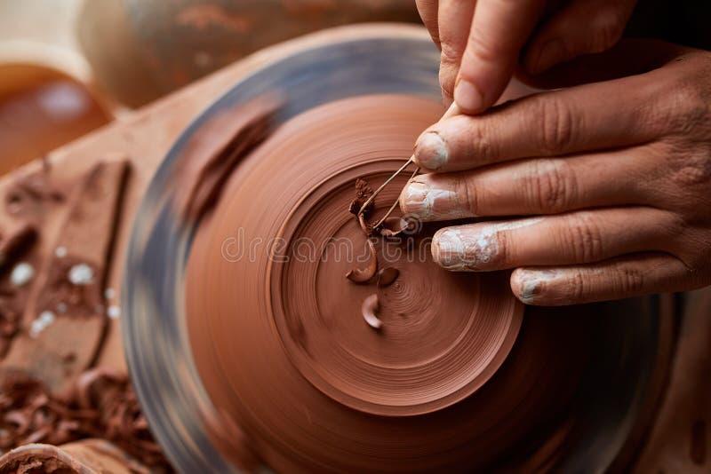 Keramikerförlage för vuxen man som modellerar leraplattan på hjulet för keramiker` s Den bästa sikten, closeup, räcker endast arkivbilder