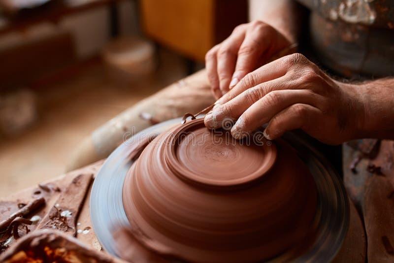 Keramikerförlage för vuxen man som modellerar leraplattan på hjulet för keramiker` s Den bästa sikten, closeup, räcker endast fotografering för bildbyråer