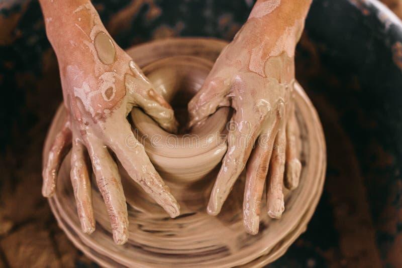 Keramikerstöpningslera på krukmakerihjulet royaltyfri bild