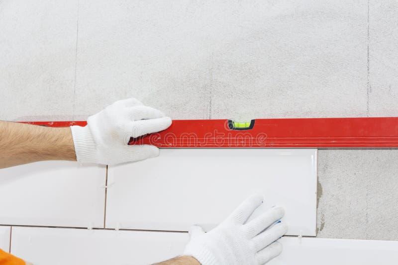 Keramikfliesen und Werkzeuge für Dachdecker, Flieseninstallation Heimwerken, Erneuerung - keramischer Fliesenbodenkleber stockbild