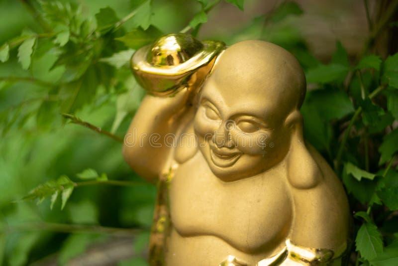 Keramisch vergoldete Statue des Wohlhabens und des Vergnügens von Hotei im Garten lizenzfreie stockbilder