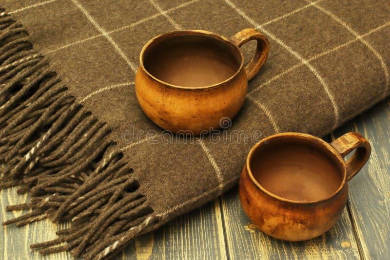 Keramische antike Schalen des Tees und weiches warmes woolen Plaid auf dunklem hölzernem Hintergrund lizenzfreie stockbilder