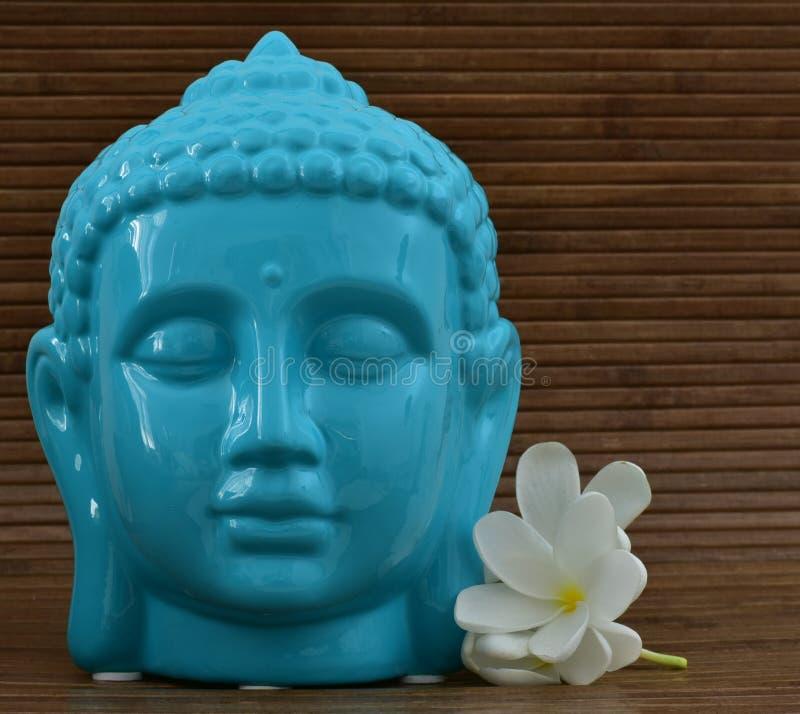 Keramische blaue Farbruhige Gesichtsstatue von Buddha mit Blumen auf hölzernem Hintergrund lizenzfreie stockfotografie