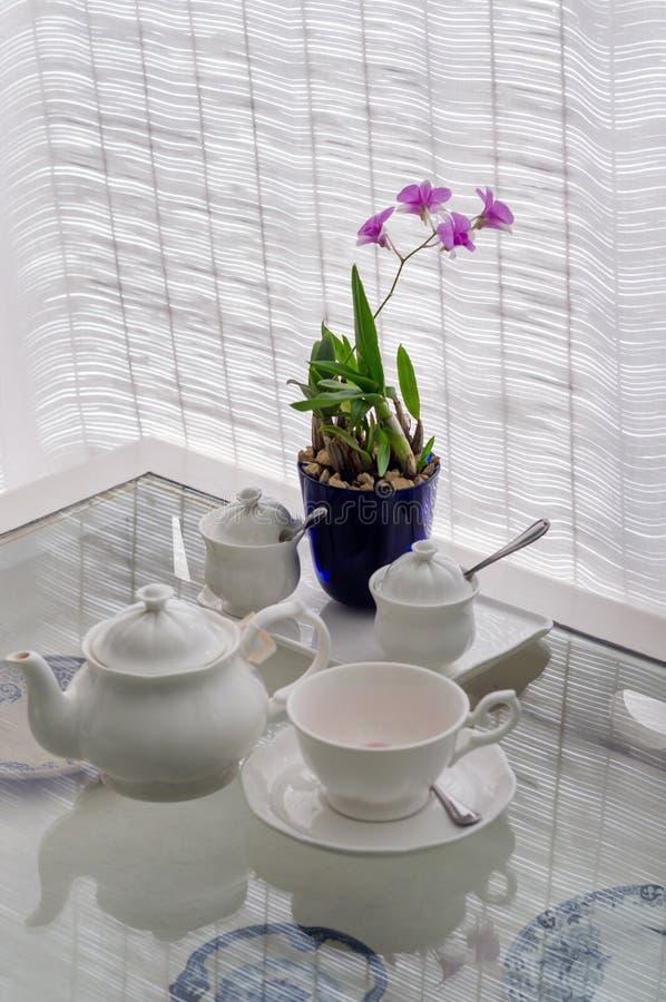 Keramische Geräte auf Tabelle mit Blume lizenzfreie stockfotos