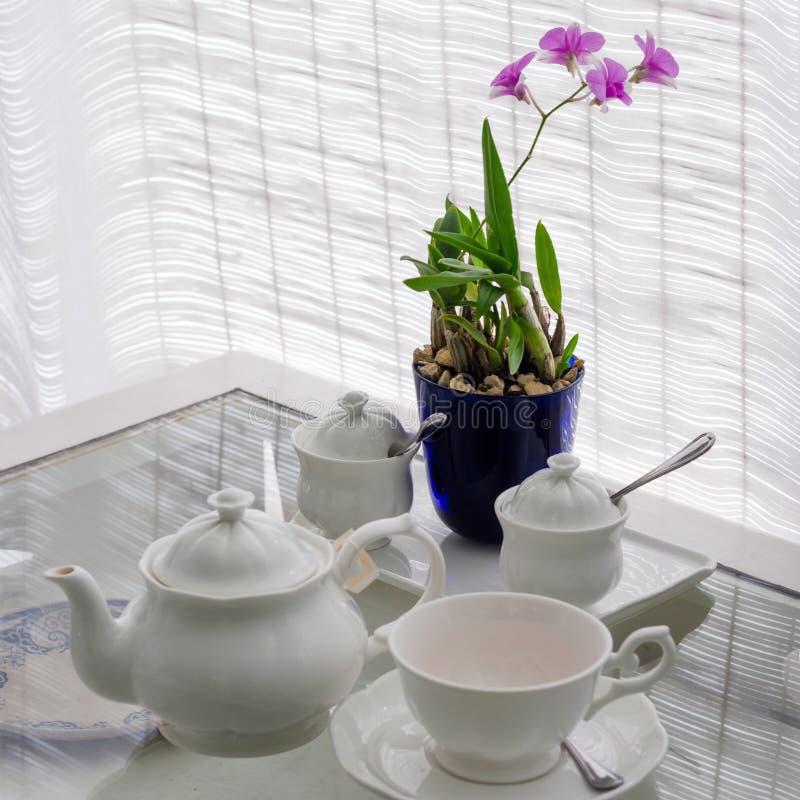 Keramische Geräte auf Tabelle mit Blumendekoration stockfotografie