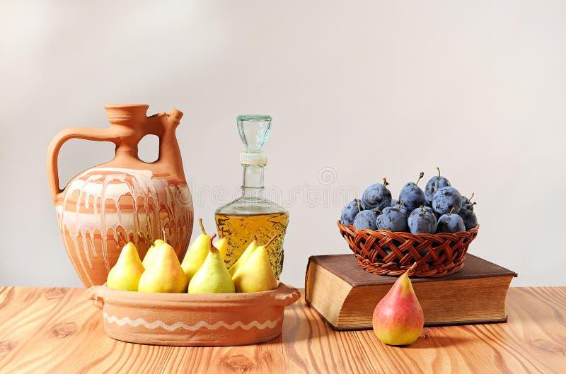 Keramische Karaffe und Früchte in einem Korb lizenzfreie stockbilder
