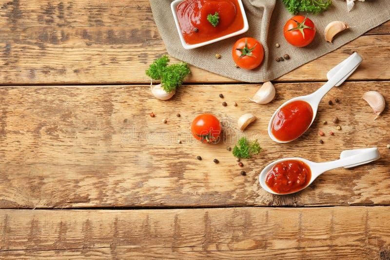 Keramische Löffel mit Tomatensauce und Gewürzen lizenzfreies stockbild