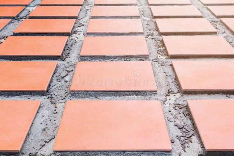 Keramische Orange der Reihenfliese auf Boden installieren mit Zement in Haus der Arbeitsbau-Erneuerung im Freien lizenzfreie stockfotos