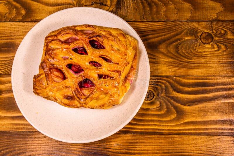Keramische Platte mit frischem Kirschstrudel auf Holztisch Beschneidungspfad eingeschlossen lizenzfreies stockfoto