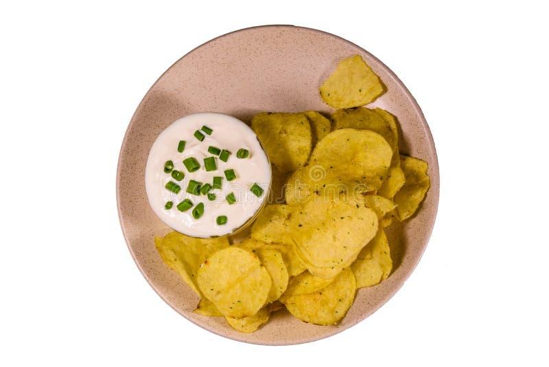 Keramische Platte mit Kartoffelchips und Glasschüssel mit dem Sahne lokalisiert auf einem weißen Hintergrund lizenzfreie stockfotografie
