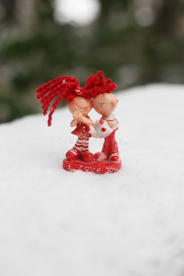 Keramische rote Statuette eines Mädchens und des Jungen im Schnee stockfotografie