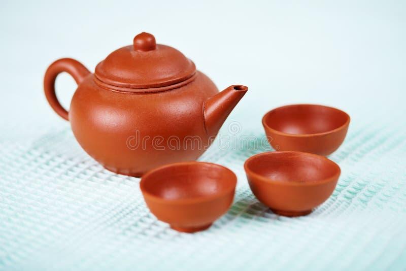 Keramische Teekanne und Cup auf blauem Tuch stockfotografie