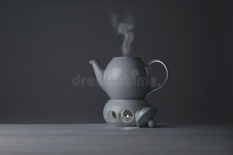 Keramische Teekanne und Wärmer mit brennender Kerze auf Tabelle lizenzfreies stockbild