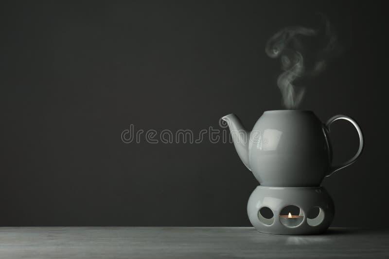 Keramische Teekanne und Wärmer mit Kerze auf Tabelle gegen grauen Hintergrund Raum f?r Text lizenzfreie stockfotografie