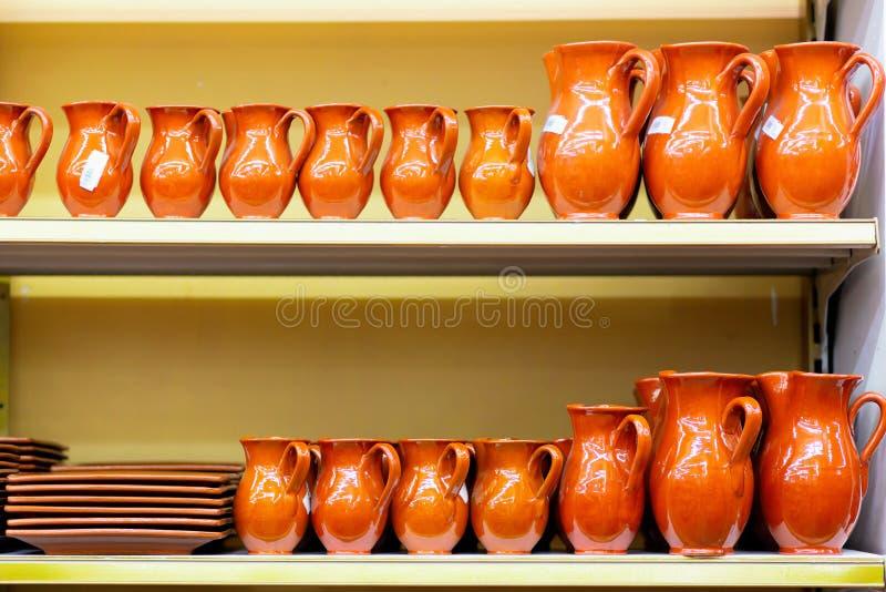 Keramische Tonwarenkrüge und -platten sind auf dem Ladenregal stockbilder