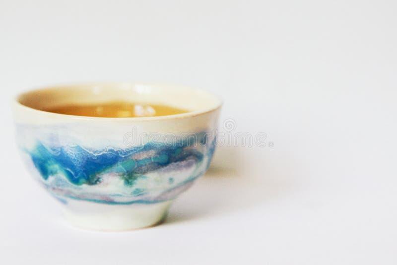 Keramische Tränke mit Tee auf einem lokalisierten weißen Hintergrund Japanische Schüssel mit einem schönen Muster stockbild