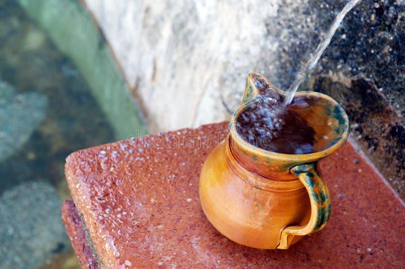Keramischer Krug, der mit natürlichem Quellenwasser, Spanien füllt lizenzfreies stockfoto