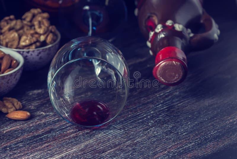 Keramischer Krug für Wein, Käse, Nüsse auf einem hölzernen Brett, Hintergrund stockbild