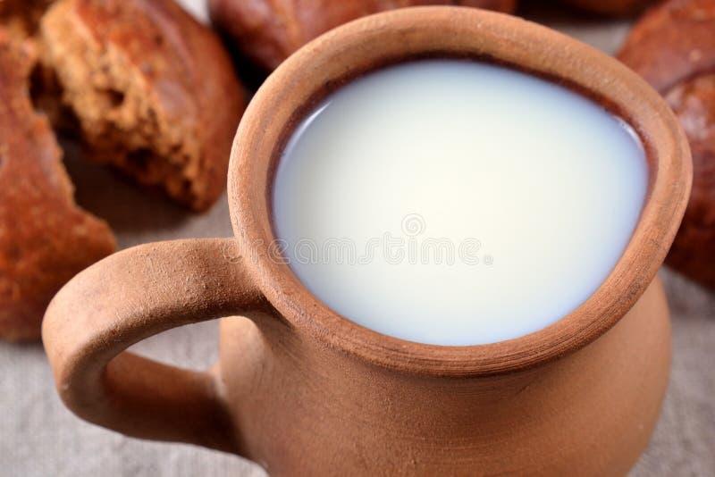 Keramischer Krug mit Milch und frischem Brot stockbild