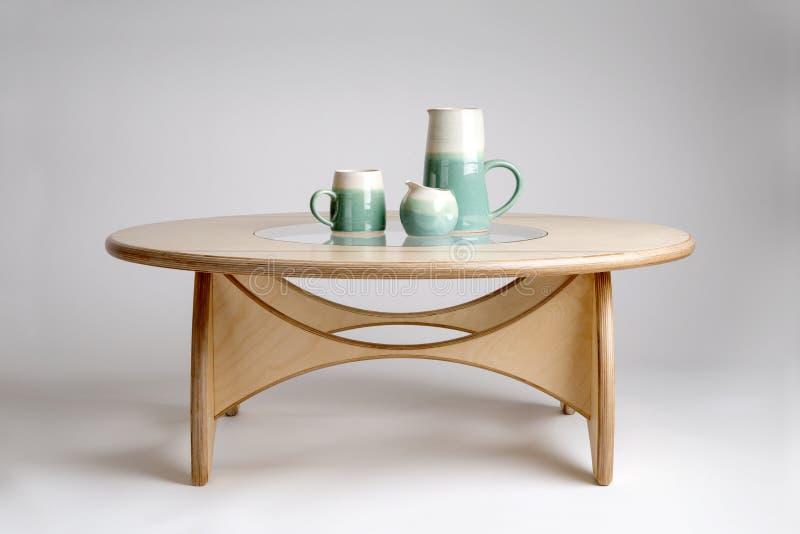 Keramisk dricka uppsättning på den naturliga Wood formgivaren Round Table arkivbilder