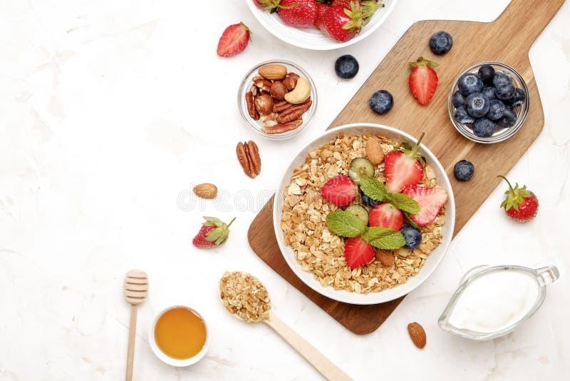 Keramisk granolabunke, blandade ingredienser på tabellen Sund näringsrik frukost med strikt vegetarianyoghurt, rå frukter, muttra royaltyfri bild