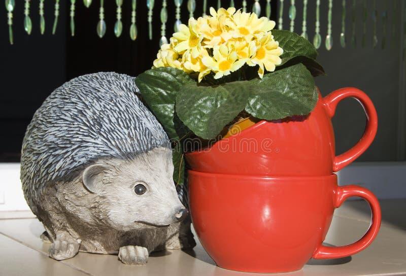Keramisk igelkott och röda koppar med blommor royaltyfri foto