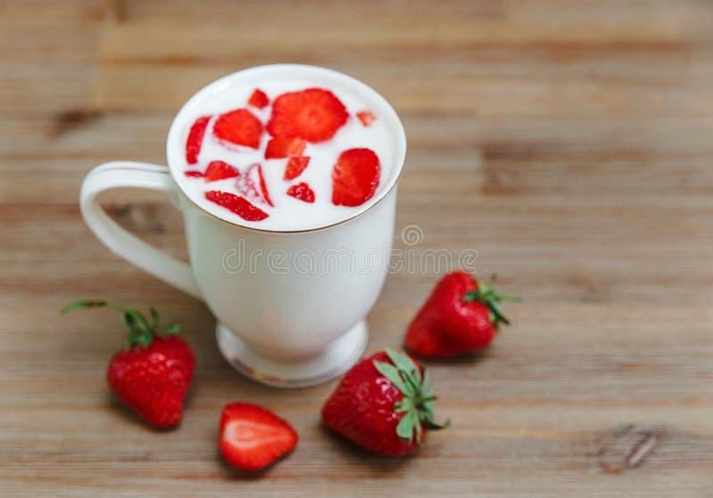 Keramisk kopp av yoghurten, röda nya jordgubbar på träbakgrunden Organisk sund smaklig mat för frukost Matlagningvitaminer Ingred royaltyfri foto