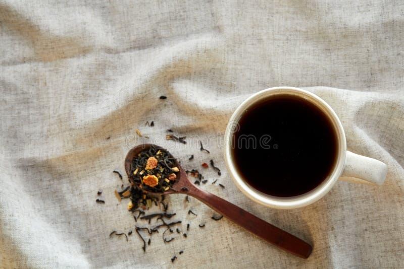 Keramisk kopp te med spridda teblad på en servett på lantlig träbakgrund, selektiv fokus arkivfoto