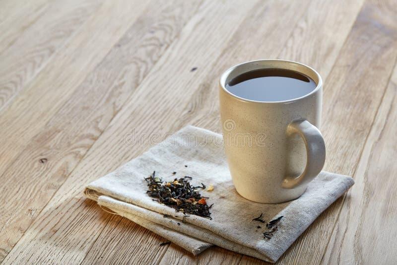 Keramisk kopp te med spridda teblad på en servett på lantlig träbakgrund, selektiv fokus royaltyfri foto