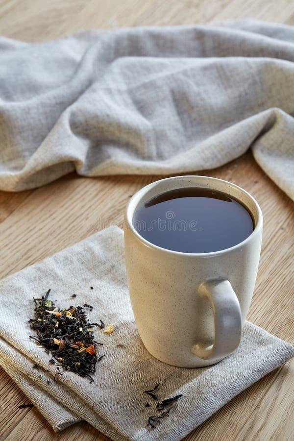 Keramisk kopp te med spridda teblad på en servett på lantlig träbakgrund, selektiv fokus arkivbilder