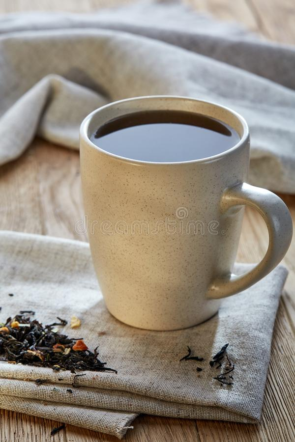 Keramisk kopp te med spridda teblad på en servett på lantlig träbakgrund, selektiv fokus royaltyfri bild