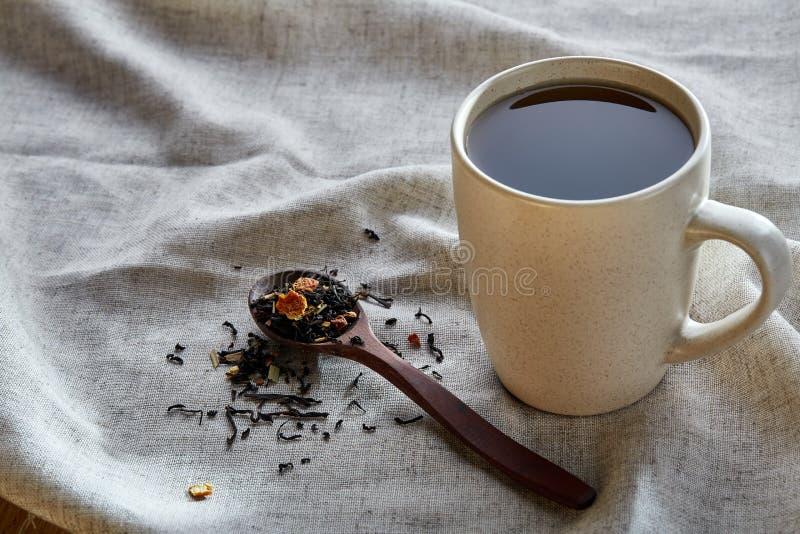 Keramisk kopp te med spridda teblad på en servett på lantlig träbakgrund, selektiv fokus arkivbild