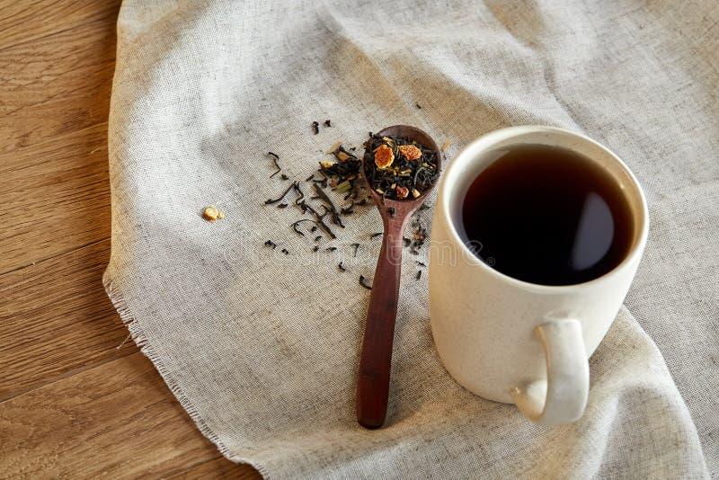 Keramisk kopp te med spridda teblad på en servett på lantlig träbakgrund, selektiv fokus royaltyfria bilder