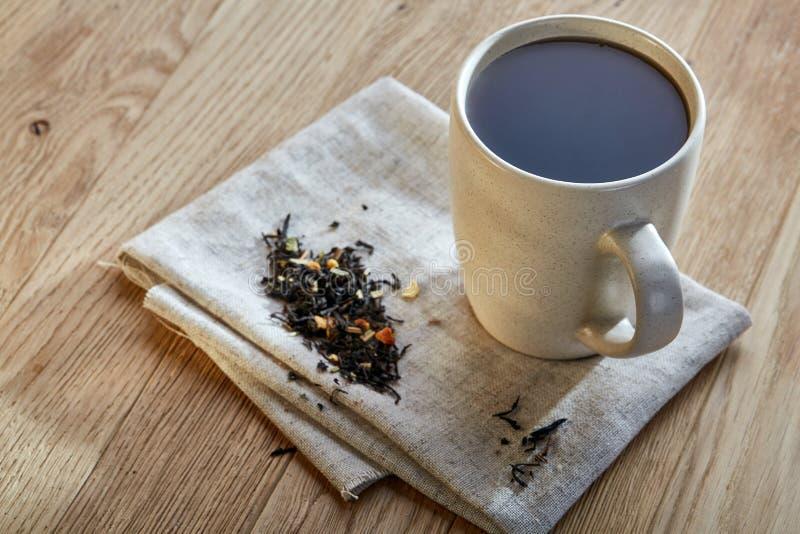 Keramisk kopp te med spridda teblad på en servett på lantlig träbakgrund, selektiv fokus royaltyfri fotografi