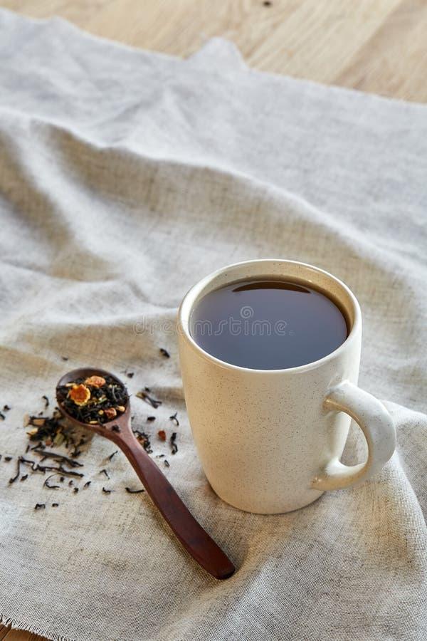Keramisk kopp te med spridda teblad på en servett på lantlig träbakgrund, selektiv fokus arkivfoton
