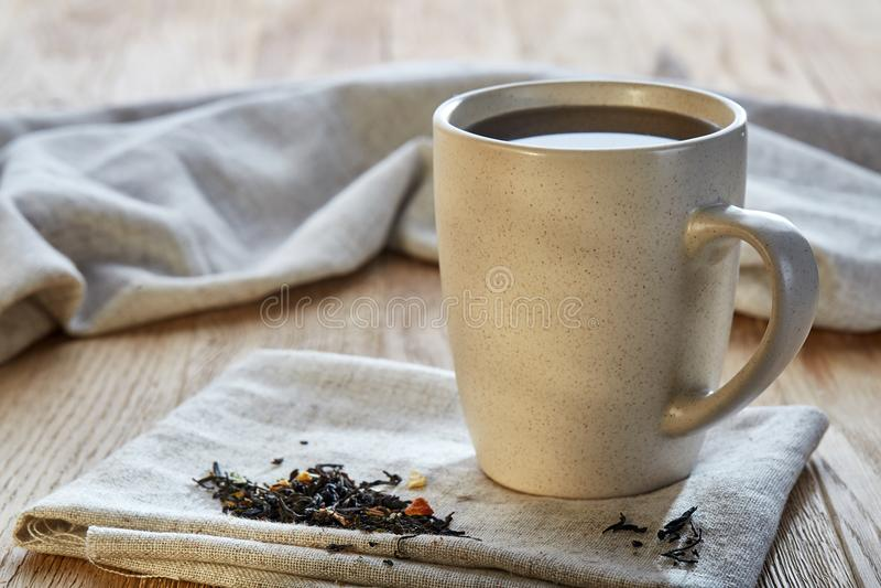 Keramisk kopp te med spridda teblad på en servett på lantlig träbakgrund, selektiv fokus fotografering för bildbyråer