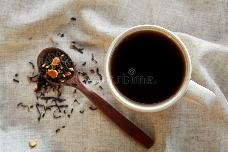 Keramisk kopp te med spridda teblad på en servett på lantlig träbakgrund, selektiv fokus royaltyfria foton