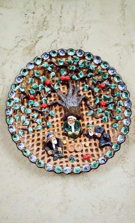 Keramisk platta med applikationer i form av uzbekiska män som sitter under ett granatäppleträd och dricker te med sconeser royaltyfri bild
