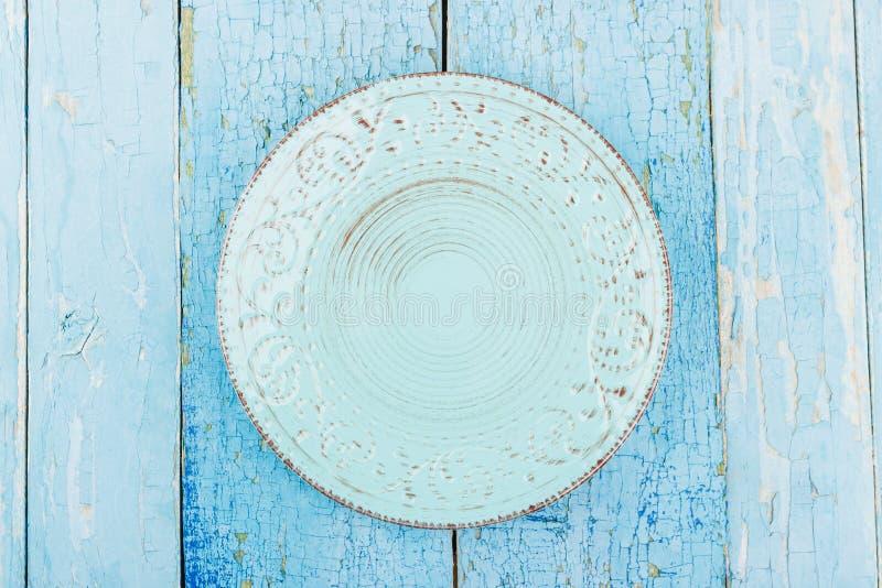 Keramisk platta med en modell på den blåa gamla träbakgrunden royaltyfria foton