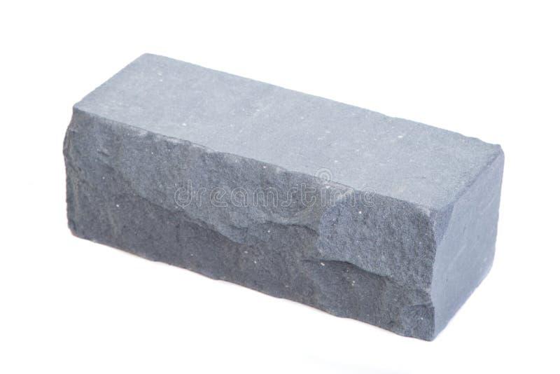Keramisk tegelsten för grå lättnad på den vita bakgrunden arkivfoton