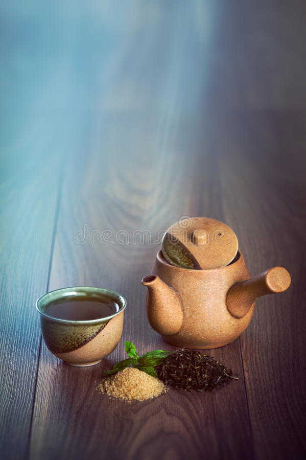 Keramisk tekanna, kopp av svart te med mintkaramellsidor och farin på trätabellen med kopieringsutrymme royaltyfri bild