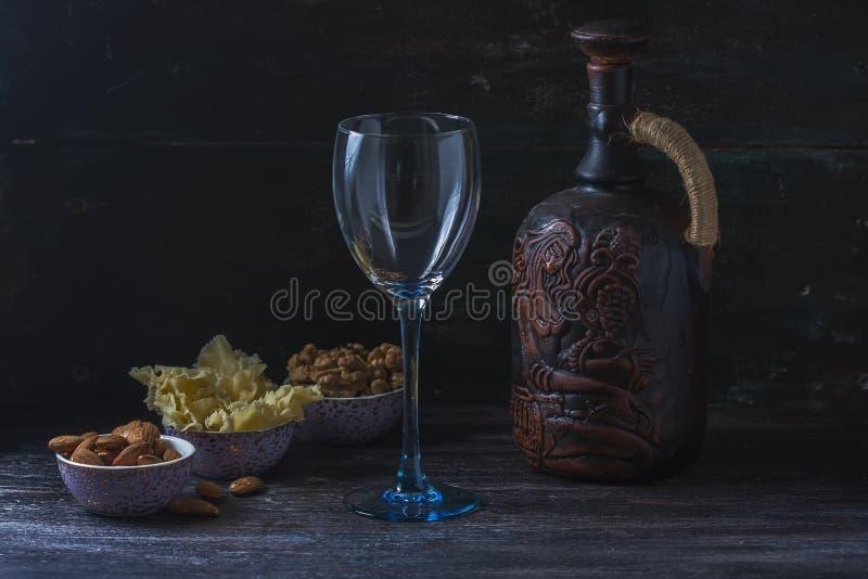 Keramisk tillbringare för vin, ost, muttrar på ett träbräde, bakgrund arkivbilder