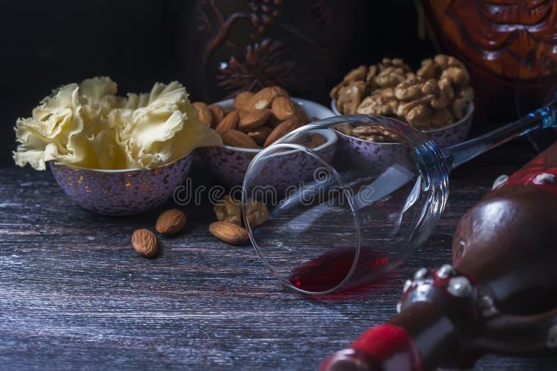 Keramisk tillbringare för vin, ost, muttrar på ett träbräde, bakgrund arkivbild
