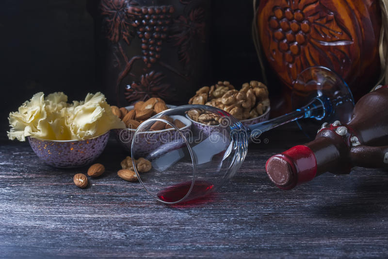 Keramisk tillbringare för vin, ost, muttrar på ett träbräde, bakgrund royaltyfri fotografi