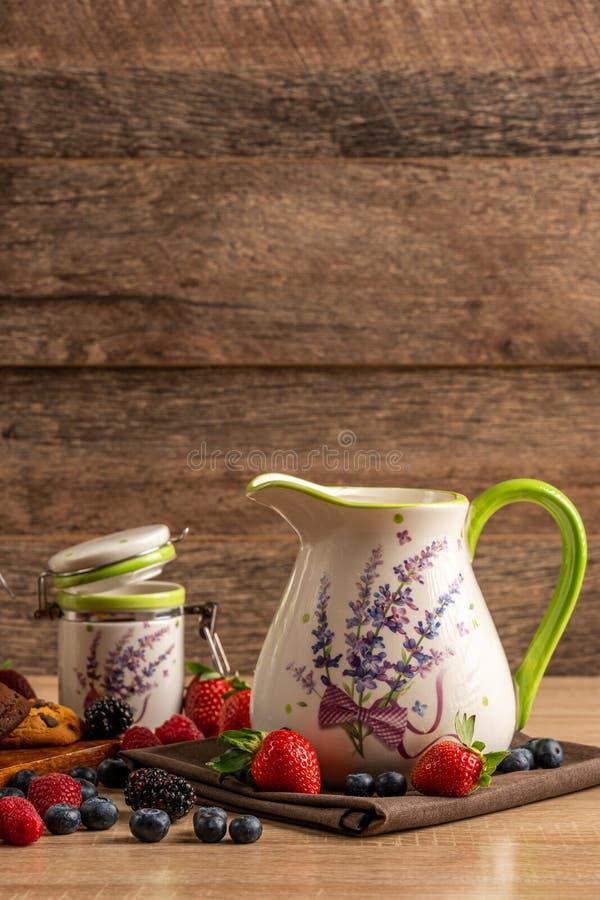 Keramisk tillbringare och keramisk krus med blandningen av skogfrukter på träbakgrund arkivbilder