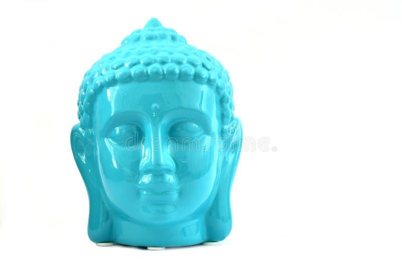 Keramiska blått färgar den fridfulla framsidastatyn av Buddha med blommor som isoleras på vit bakgrund arkivfoton