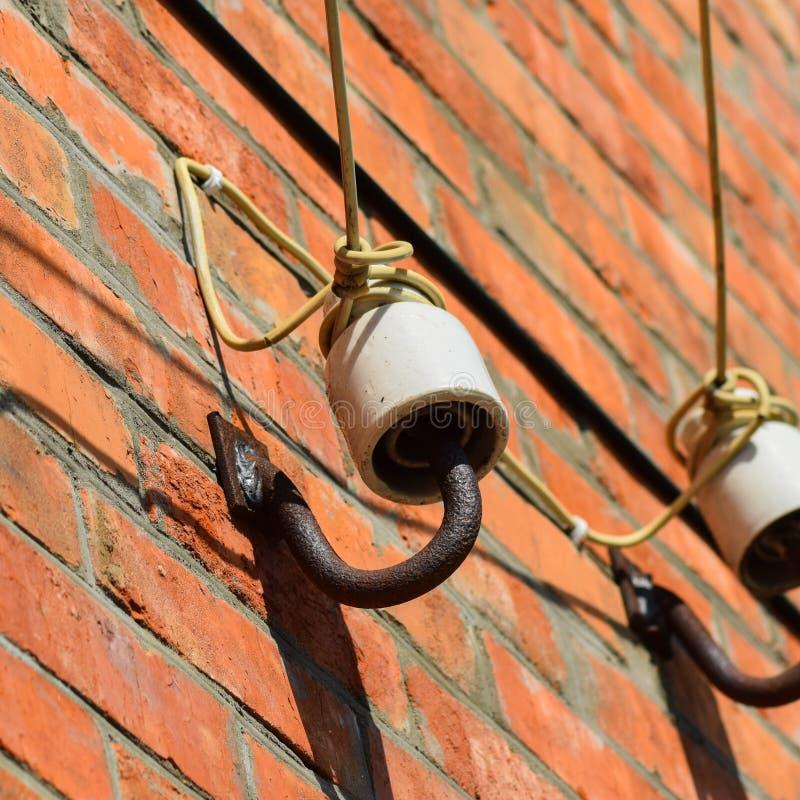 Keramiska isolatorer på väggen royaltyfri fotografi