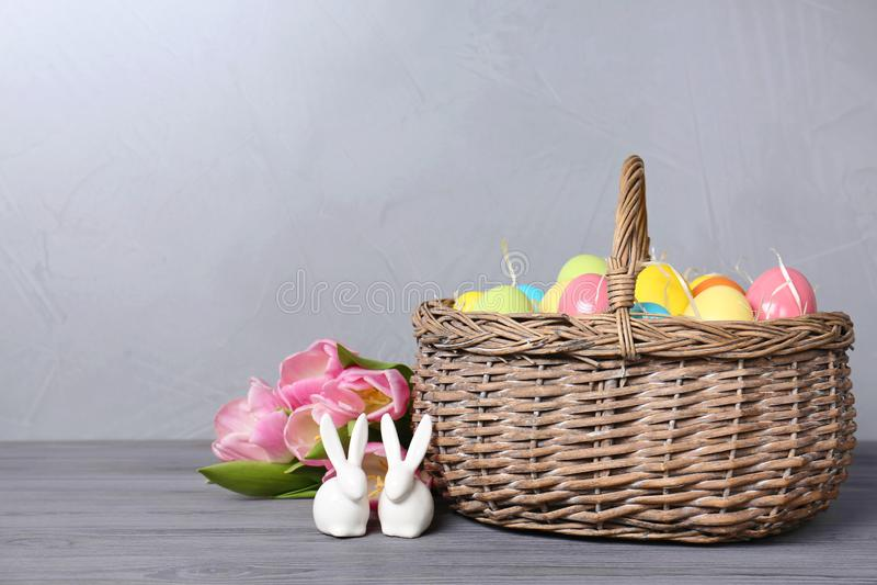 Keramiska kaniner nära vide- korg med påskägg och vårtulpan på trätabellen mot ljus bakgrund fotografering för bildbyråer