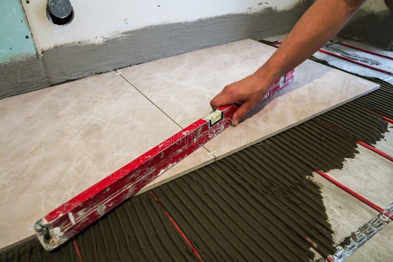 Keramiska tegelplattor och hjälpmedel för tiler Arbetarhand som installerar golvet royaltyfri bild