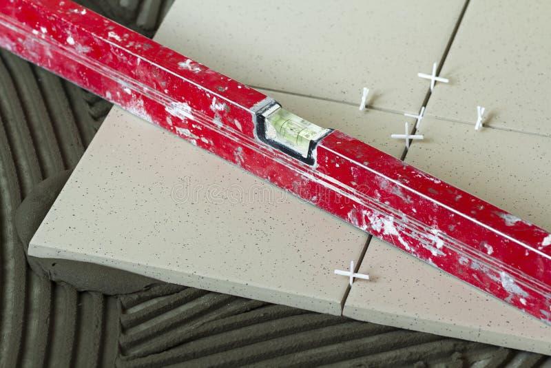 Keramiska tegelplattor och hjälpmedel för tiler Installation för golvtegelplattor Hemförbättring renovering - bindemedel för golv royaltyfri fotografi
